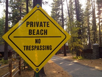 A sign alongside a road indicating a private beach.