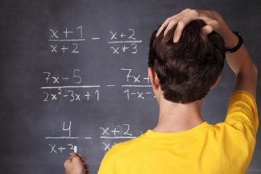 A school boy solving a math problem.