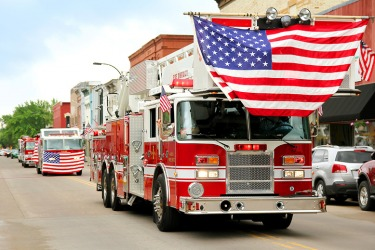 A procession of fire trucks in a small town parade.