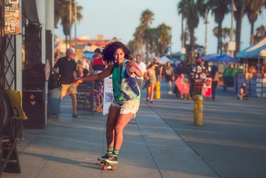 A young woman skateboarding on the promenade of the Venice Beach boardwalk.
