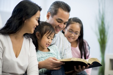 The parents promulgate the lessons in the Bible to their children by reading together.