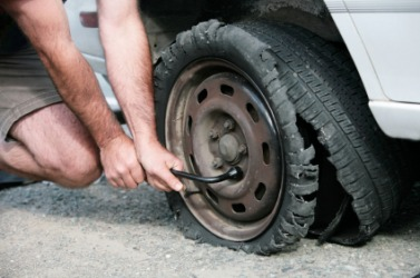 A man changing a tire after a blowout.