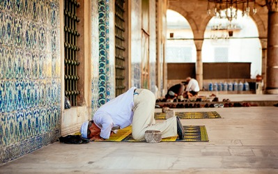 Man offering Namaz at mosque by taking on a prostrate position.