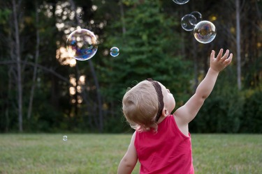 The young child protracts her arm to touch the bubbles.