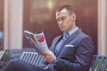 A businessman is reading a magazine publication.