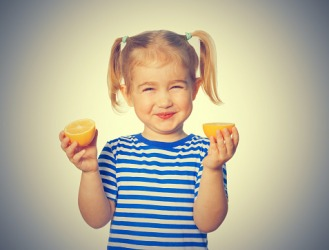 The young girl's face puckers while eating a lemon.