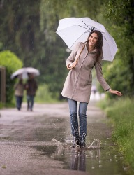A woman walking in a puddle on a rainy day.