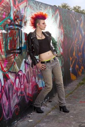A stylish punker standing against a graffiti wall.