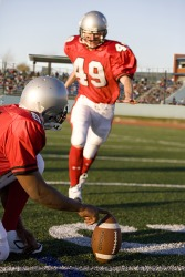 The football player punts the ball.