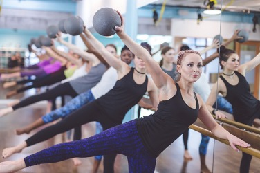The members are challenged by the workout routine in the Pure Barre class at the local gym.