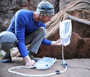 He uses a device to purify water in order to make it safe to drink while hiking in remote areas.
