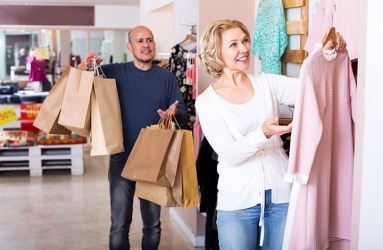 The pussy whipped husband held his wife's bags while she shopped.