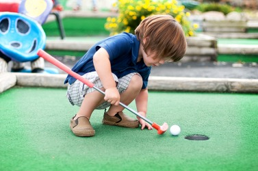 A young boy playing put put golf.
