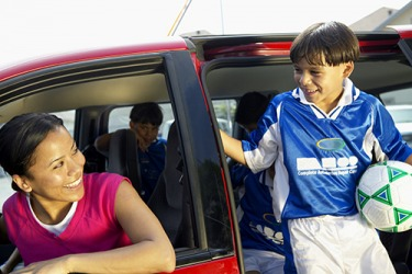She is the quintessential soccer mom because she takes her son and his friends to soccer practice  in her minivan.