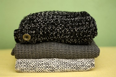 The top and bottom sweaters in the stack are woven in a ragg pattern.