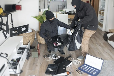 The thieves ransack a home looking for valuables.