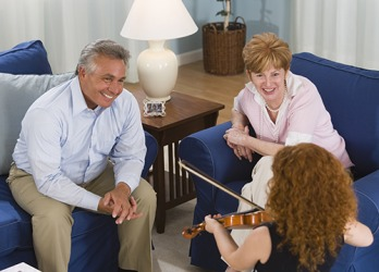 The grandparents listened with rapt attention to their granddaughter's violin performance.