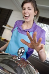 She reacted by pulling her hand away quickly when she touched the hot lid.