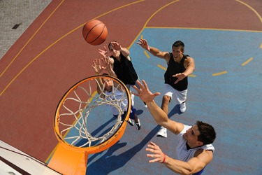 The basketball players fought each other to get the rebound.