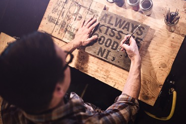 Tim reclaims scrap wood to create one-of-a-kind artistic signs.