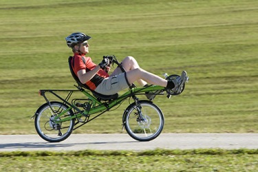 Jim always wears his helmet when he rides his recumbent bike .
