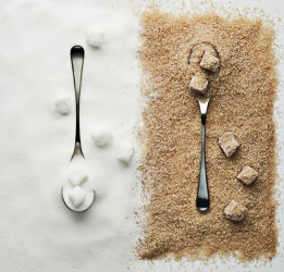The refined white sugar is on the left, whereas the raw sugar on the right has a tan color.