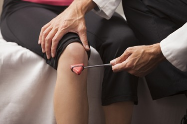 The doctor is performing a test of the patellar reflex on the patient.