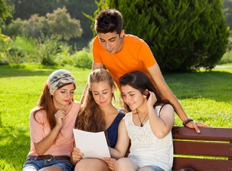 Lisa and her friends carefully read the letter regarding her acceptance to the college that she applied to at the beginning of her senior year in high school.