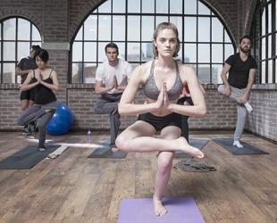 The yoga teacher showed the class how to do a toe stand pose.