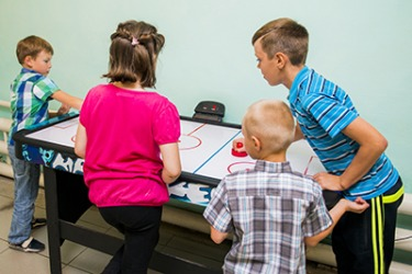 The only sounds in the room are the hum of the air hockey table and the back and forth clack of the puck.