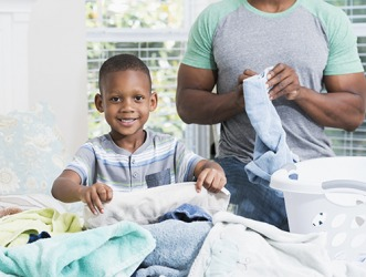 Devon is very helpful around the house and is eager to take responsibility for helping his dad fold the laundry.