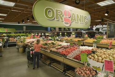 The retail marketing for the organic produce department includes a large hanging sign with colors that represent healthy food.