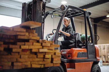 Theresa shifted the forklift into reverse after loading up the stack of wood.