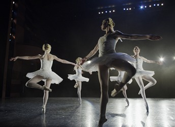 The ballet dancers revolve in unison while pirouetting during their performance on stage.