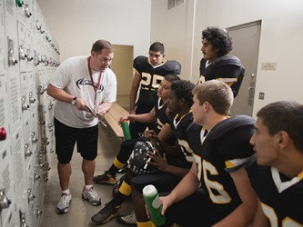 The rivalry between the high school football teams is intense, so the coach goes through the plays one more time before the start of the game.