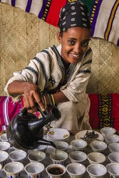 An Ethopian woman pouring robust coffee into cups.