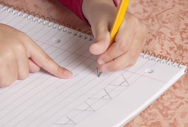 The young student is learning the alphabet by rote while also improving manual dexterity writing the letters by hand.