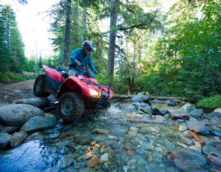 An ATV is the type of vehicle suitable for traversing rugged, off-road trails.