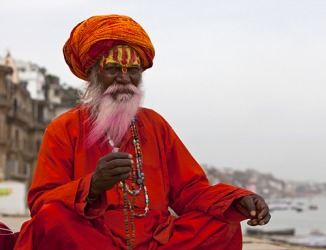 The Indian Sadhu has the characteristic face painting and wears the traditional colors of his people.