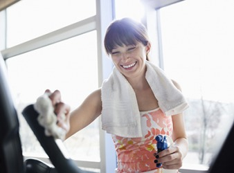 Natalie uses a sanitary spray and cloth to wipe down the exercise equipment at the gym before and after she uses it.