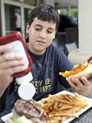 Josh was famished after his rigorous football practice so he ordered the large hamburger and french fries to hopefully sate his appetite.