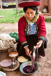 The Peruvian woman saturates the wool yarn with a natural purple dye in preparation for weaving colorful textiles.