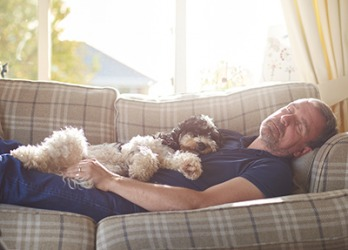 On days when Roy schlumps on the couch all afternoon, his dog Millie is happy to keep him company.