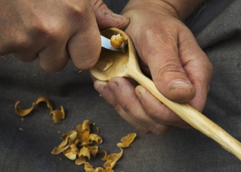 The craftsman uses a hand tool to sculp a wooden spoon.