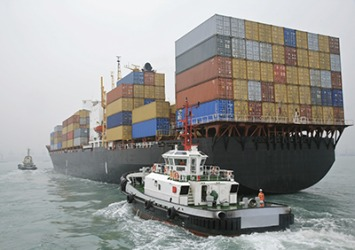 A tugboat helps a cargo ship maintain a safe amount of sea room when entering and leaving a harbor.