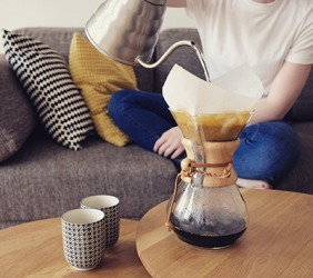He pours hot water into the filter so that it can slowly seep through the coffee grounds to make a pot of fresh coffee.