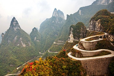 The serpentine mountain road in China leads to Tianmen Cave at the top.