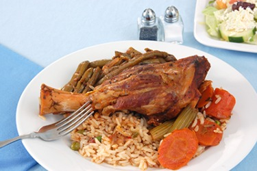 A Greek style roast lamb shank with green beans, carrots and rice pilaf.