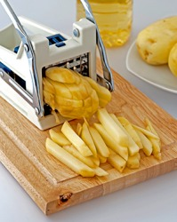 When the potato is pushed through the metal grid, the shearing stress cuts it into sticks to make french fries.