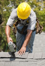 A worker is nailing shingles on the roof of a house.